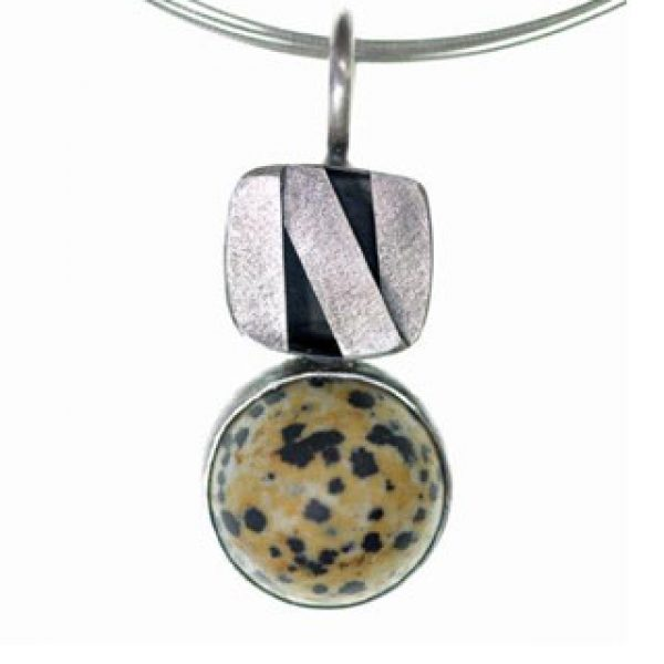 This brushed sterling silver and river rock pendant is handmade by silversmith Terrli Logan