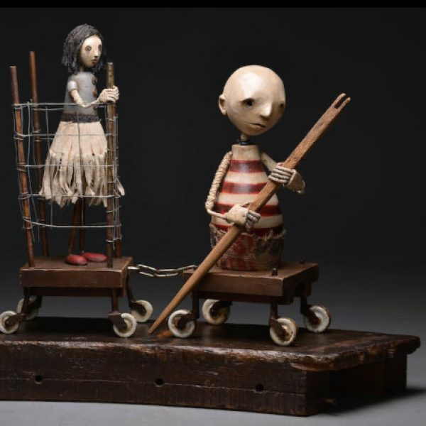 The collector is a mixed media sculpture by Trent Manning. It features two macabre characters on a long journey.