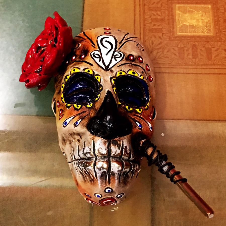 Alma Hermosa is a limited edition, bronze mask by artist Bryan Tubbs. This pieces features a female face painted for the traditional Latin American Day of the Dead, honoring the spiritual journey of your relatives who have passed before you. She has a bright red rose on her head.