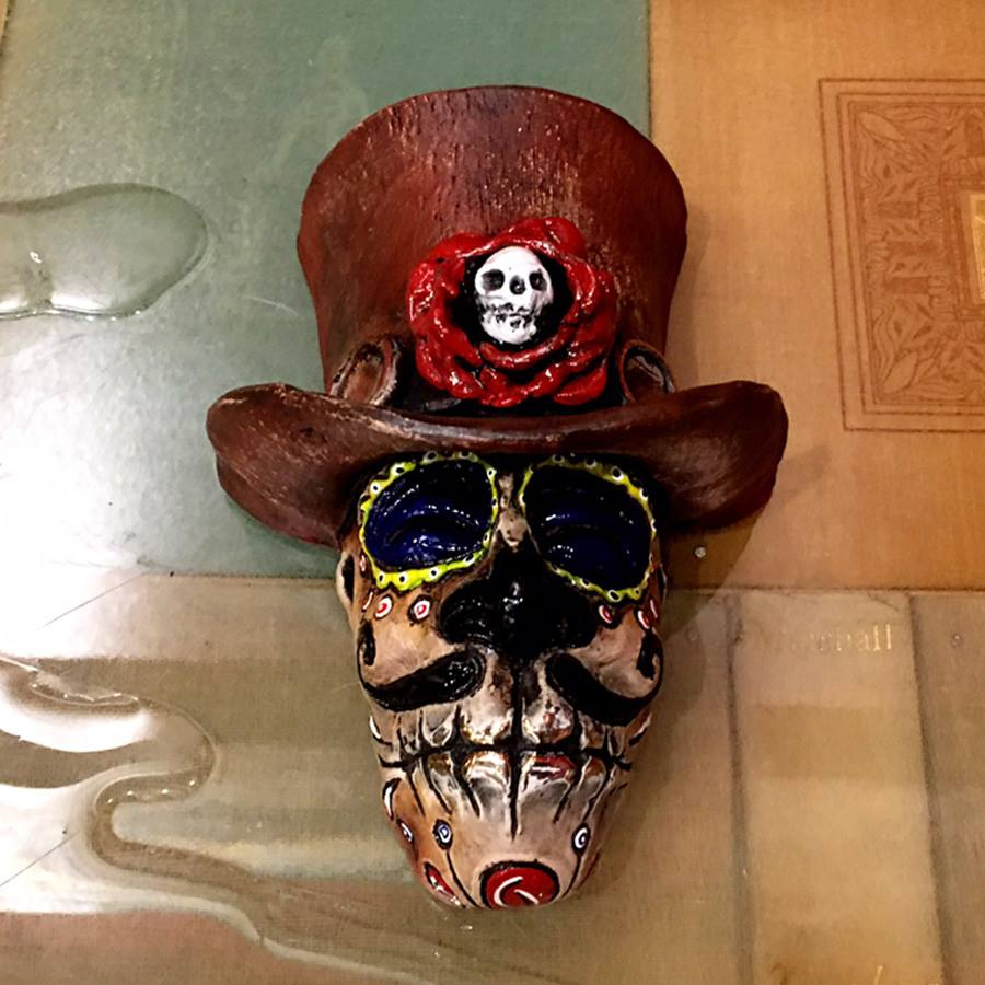 Amado Hasta La Muerte is a limited edition bronze mask by Bryan Tubbs it features a male face and top hate Day of the Dead costume.