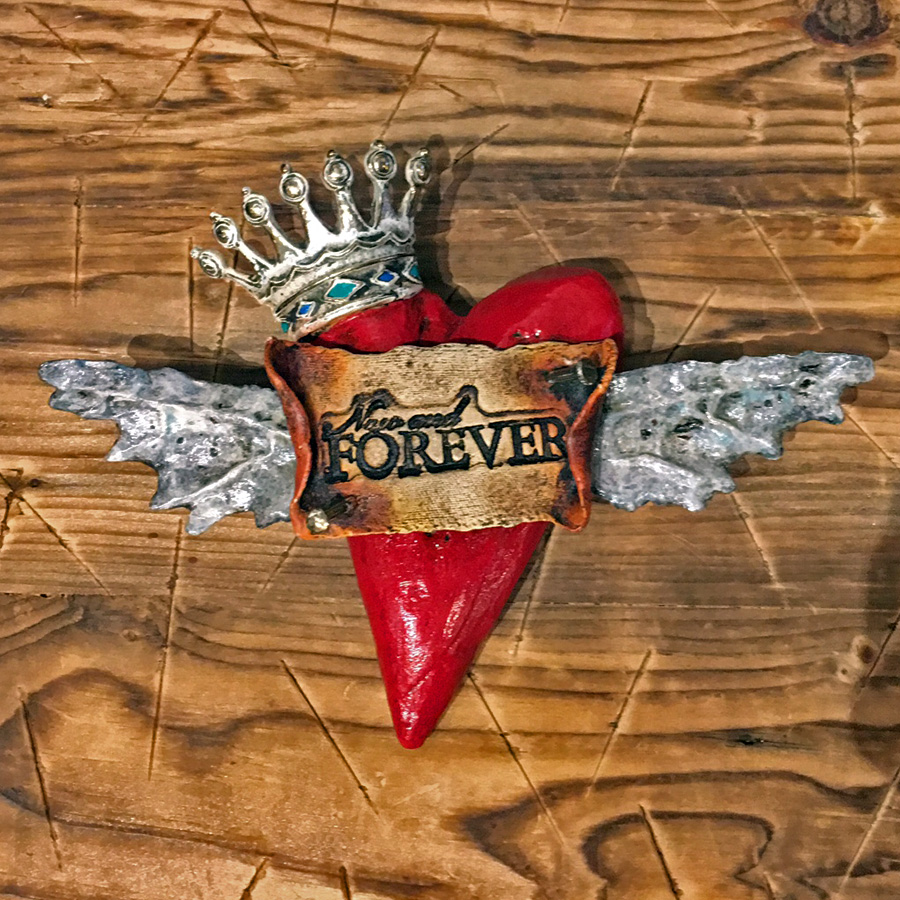 """This is a bronze heart by artist Bryan Tubbs. It features a bright red heart with wings and a crown. A banner over the front of the heart reads """"Now and Forever."""""""