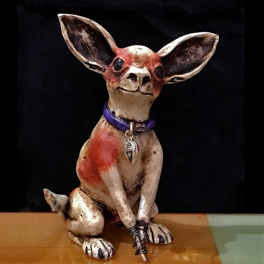 Perrita Bonita is a limited edition bronze Chihuahua by Bryan Tubbs. This lovely K9 has a light brown to burnt orange patina, purple collar with a silver locket around her neck. Her ears are perched and her head is titled like she's just discovered something new.